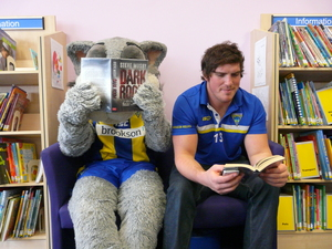 Warrington Wolves player and mascot reading.jpg